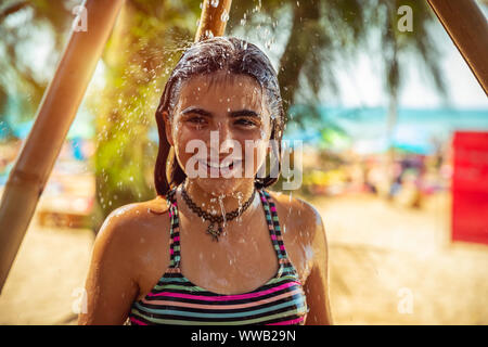 Retrato de una hermosa niña en la playa, niño feliz tomar una ducha en la playa, divertirse al aire libre, disfrutando de sus vacaciones de verano