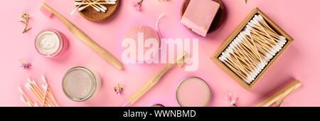 Libre de plástico, cero residuos cosméticos, plano panorámico yacía sobre un fondo de color rosa. Cepillos de dientes de bambú, hisopos de algodón, esponja konjac, productos orgánicos