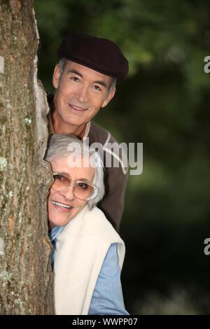 Pareja de ancianos escondido detrás de un árbol