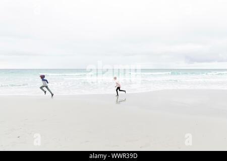 Chico y chica corriendo en la playa en Carmel, California