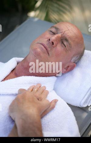 Hombre sujetando la mano de su esposa mientras duerme