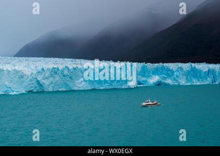Barco turístico en el frente del Glaciar Perito Moreno en el Parque Nacional Los Glaciares, declarado Patrimonio de la Humanidad por la UNESCO, Provincia de Santa Cruz, Patagonia, Argentina Foto de stock