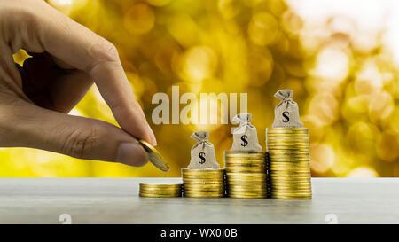 Hacer dinero y su inversión, ahorro concepto. Un hombre con la mano en el aumento de la pila de monedas con la bolsa de dinero y fondo dorado. Representa invertir a largo plazo