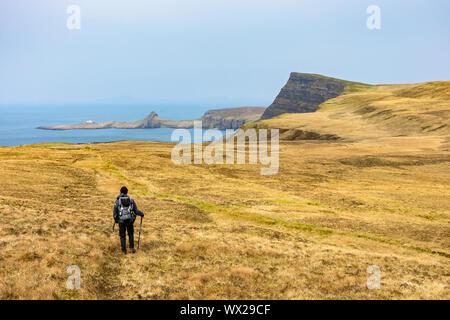 Un caminador hacia Waterstein Head y Neist point de las cuestas sobre acantilado Ramasaig Duirinish, Isla de Skye, Escocia, Reino Unido