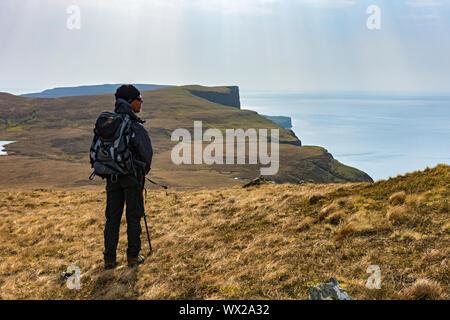 Un andador en las laderas orientales de Waterstein cabeza mirando al sur a Ramasaig Cliff y la azada, Duirinish, Isla de Skye, Escocia, Reino Unido Foto de stock