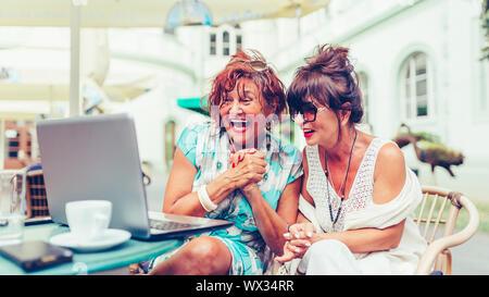 Dos mujeres senior excitado leer buenas noticias en línea sobre el ordenador portátil mientras está sentado en un café al aire libre.