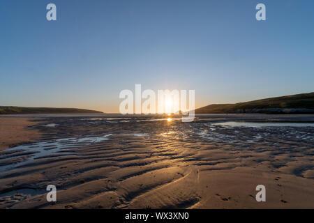 Fotografía de paisaje de la puesta de sol sobre la playa Crantock en Cornwall.