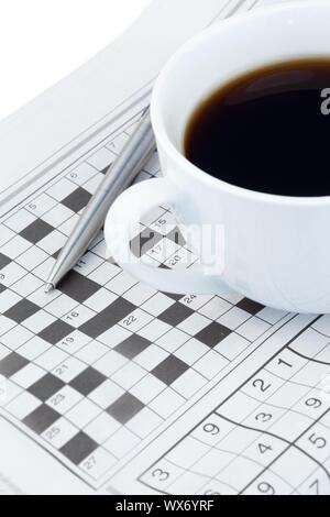Periódicos y crucigrama sobre un fondo blanco.
