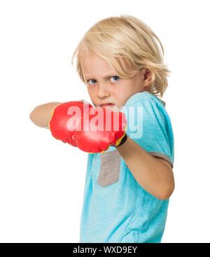 Un muchacho joven asustado y enojado usando guantes de boxeo. Aislado en blanco. Foto de stock