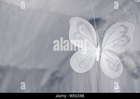 Cerca de una mariposa de color blanco artesanal colgantes con plata reluce hechas de materiales pura. El enfoque selectivo. Copie el espacio a la izquierda.