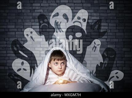 Niño asustado con linterna escondido debajo de una manta. Scary Halloween Monstruos Fantasmales en la pared. Asustado cabrito en pijamas en su cama, en su casa. Miedo