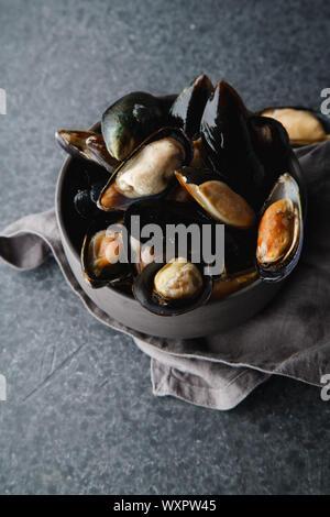Mejillones frescos en cuenco de cerámica negro sobre fondo de hormigón oscuro
