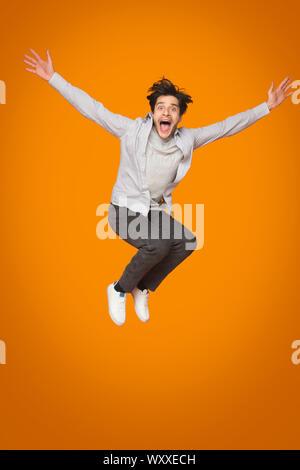 Crazy Man saltando con brazos levantados sobre fondo naranja