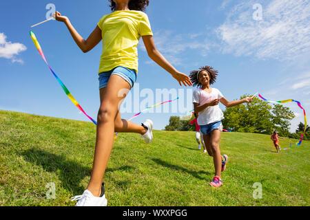 Cerrar Foto de niños felices con cintas correr en el parque