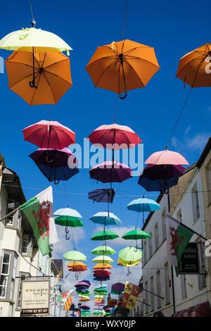 Instalación de arte colorido despliegue de paraguas colgando sobre una calle estrecha en el casco antiguo de la ciudad. Palace Street (Stryd y Plas) Gwynedd Caernarfon Gales UK