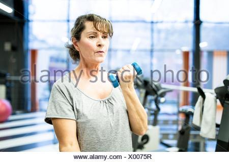 Liberados de la propiedad. Modelo liberado. Mujer sosteniendo Senior pesa en el gimnasio.