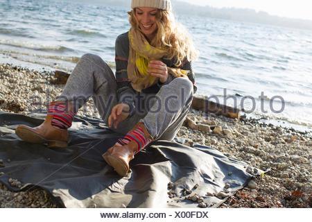 Mujer sentada en la playa ventosa Foto de stock