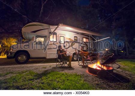 Adulto medio par y hija sentado en frente de una fogata en la noche