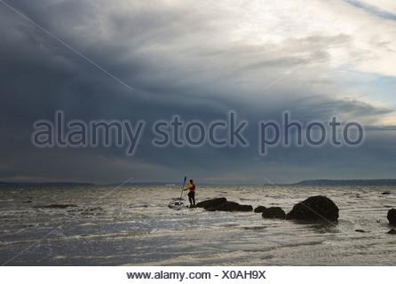 Un hombre parado sobre una roca en medio del Puget Sound con su kayak de mar flotando junto a él