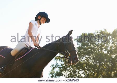 Ángulo de visión baja de chica en caballo en campo