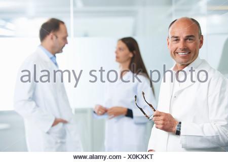 Médico varón por pared reflectante, colegas en segundo plano.