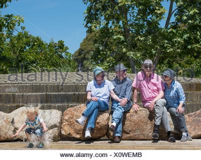 Los abuelos sentados en el parque y nieto chapoteando en el agua