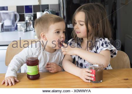 Cata de jóvenes hermanos contenido de frascos con sus dedos