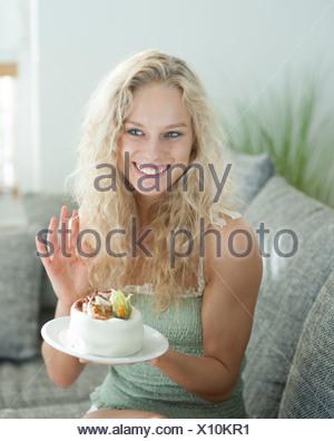 Mujer alegre y gesticulando mientras mantiene la torta en casa Foto de stock