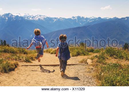 Dos chicos vestidos como superhéroes corriendo por un sendero de montaña