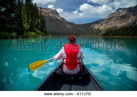 Mujer canotaje en el lago Esmeralda, el Parque Nacional Yoho, British Columbia, Canadá