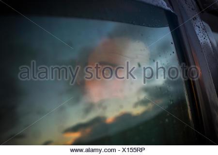 Un hombre sentado en un coche mirando afuera. Reflexiones sobre el cielo del atardecer en la ventana.