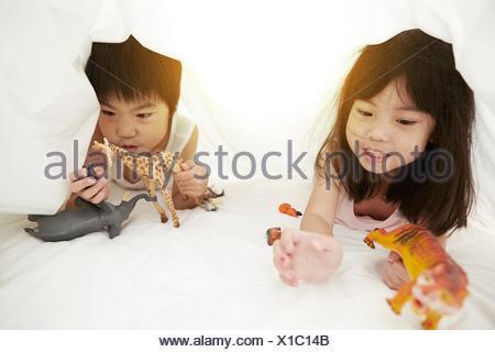Los jóvenes chinos chico y chica en la cama jugando con sus juguetes, bajo las sábanas de la cama