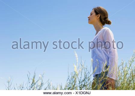 Mujer joven de pie en el pasto alto con los ojos cerrados, vista lateral