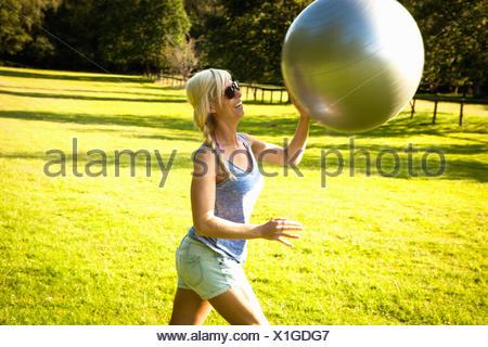 Mujer joven jugando con ejercicio de pelota en el campo