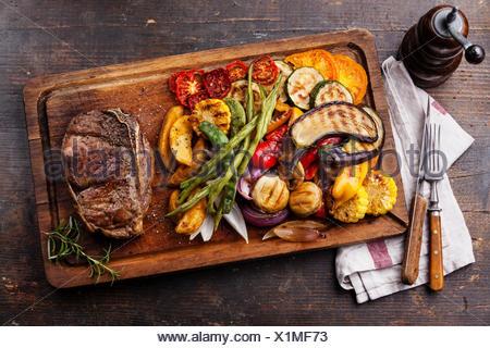 Club de bistec de carne y verduras asadas en placa de corte sobre fondo de madera oscura.