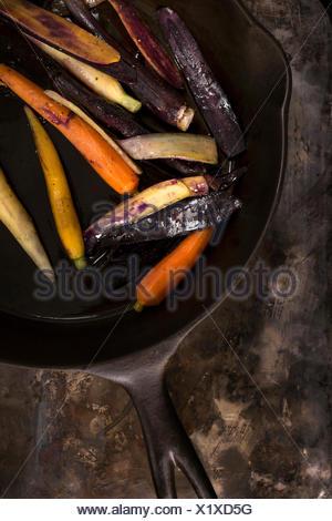 Sartén rainbow las zanahorias en un sartén de hierro fundido sobre una superficie metálica de estilo rústico.