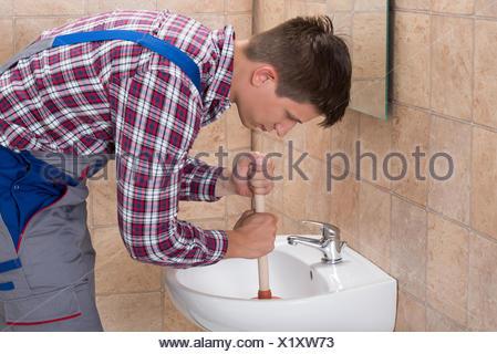 El fontanero con el émbolo en el lavabo del baño Foto & Imagen De ...