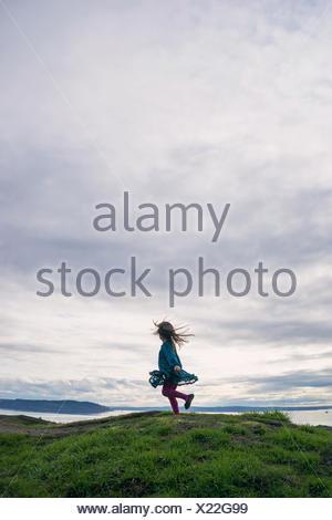 Chica girando en torno a una colina