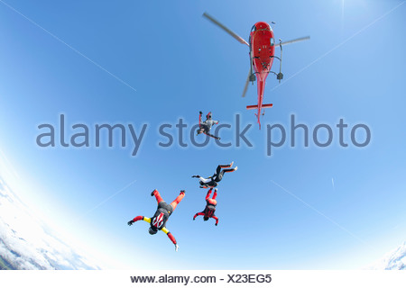 Equipo de paracaidismo en caída libre desde cuatro helicópteros Foto de stock