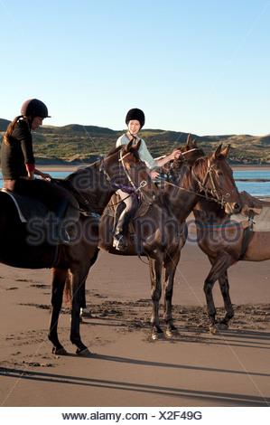 Dos mujeres a caballo en la playa