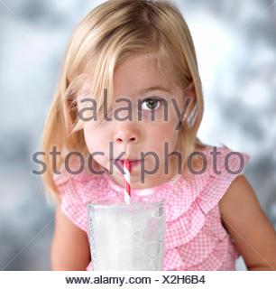 Retrato de mujer niño soplando burbujas en la leche a través de paja para beber
