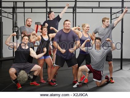 Retrato de ocho personas flexionando los músculos en el gimnasio