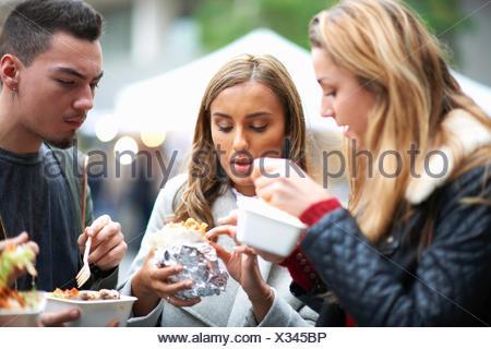 Grupo de jóvenes adultos de comer comida para llevar, al aire libre Foto de stock