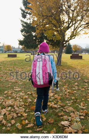 Una chica joven llevando su monopatín, camina a casa desde la escuela en un día de otoño.