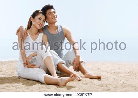 Pareja romántica sentado en la playa