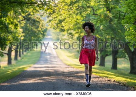 Una mujer caminando por una senda arbolada.