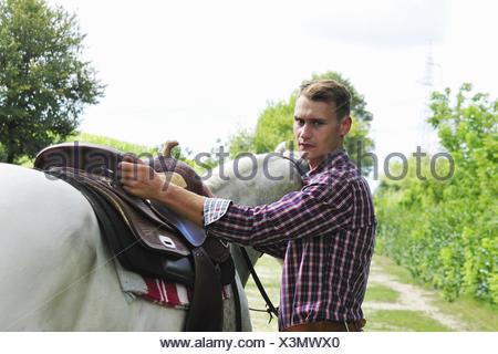 Retrato de joven ensillar caballos