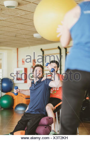 Joven practicando con pesas durante sesiones de fisioterapia Foto de stock