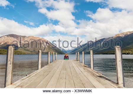 Mujer sentada en el muelle, la vista del lago Rotoiti, Parque Nacional de Los Lagos de nelson, distrito de Tasmania, Southland, Nueva Zelanda