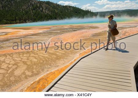 Una mujer caminatas junto al Grand Prismatic Springs, el Parque Nacional Yellowstone, Wyoming.